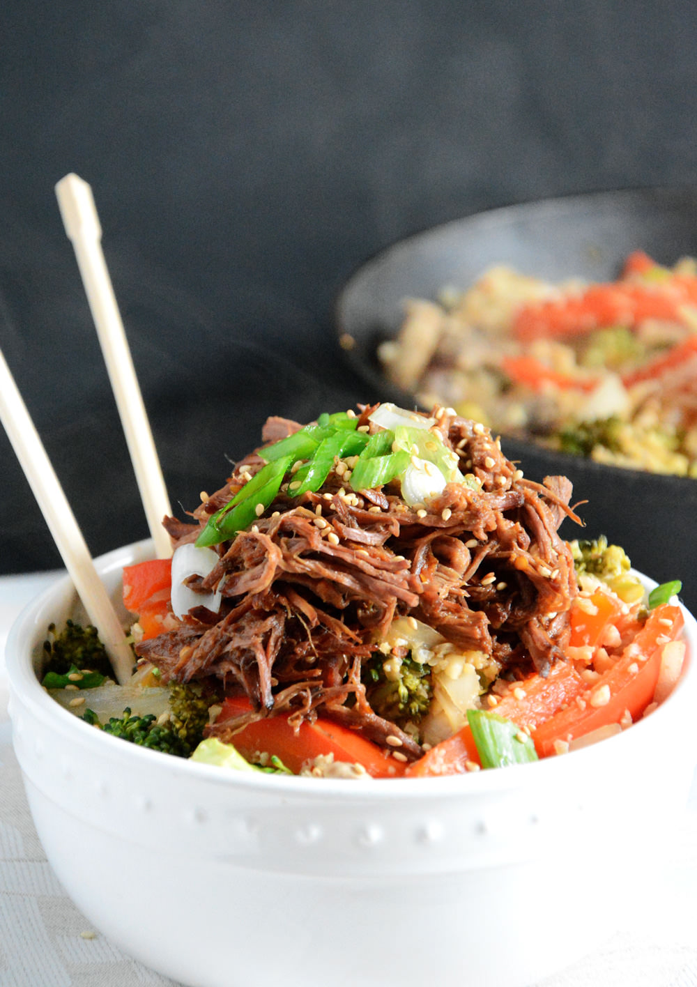 Asian beef simmered in the slow cooker until tender and served over low-carb cauliflower fried rice!
