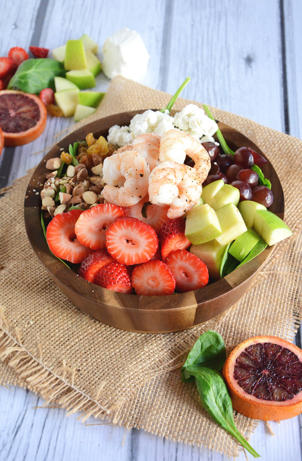 A vibrant salad with roasted shrimp, packed with fresh fruit, creamy goat cheese and roasted almonds and topped with a sweet citrus dressing made from blood oranges and sweetened with honey. This salad is colorful, healthy, and delicious!
