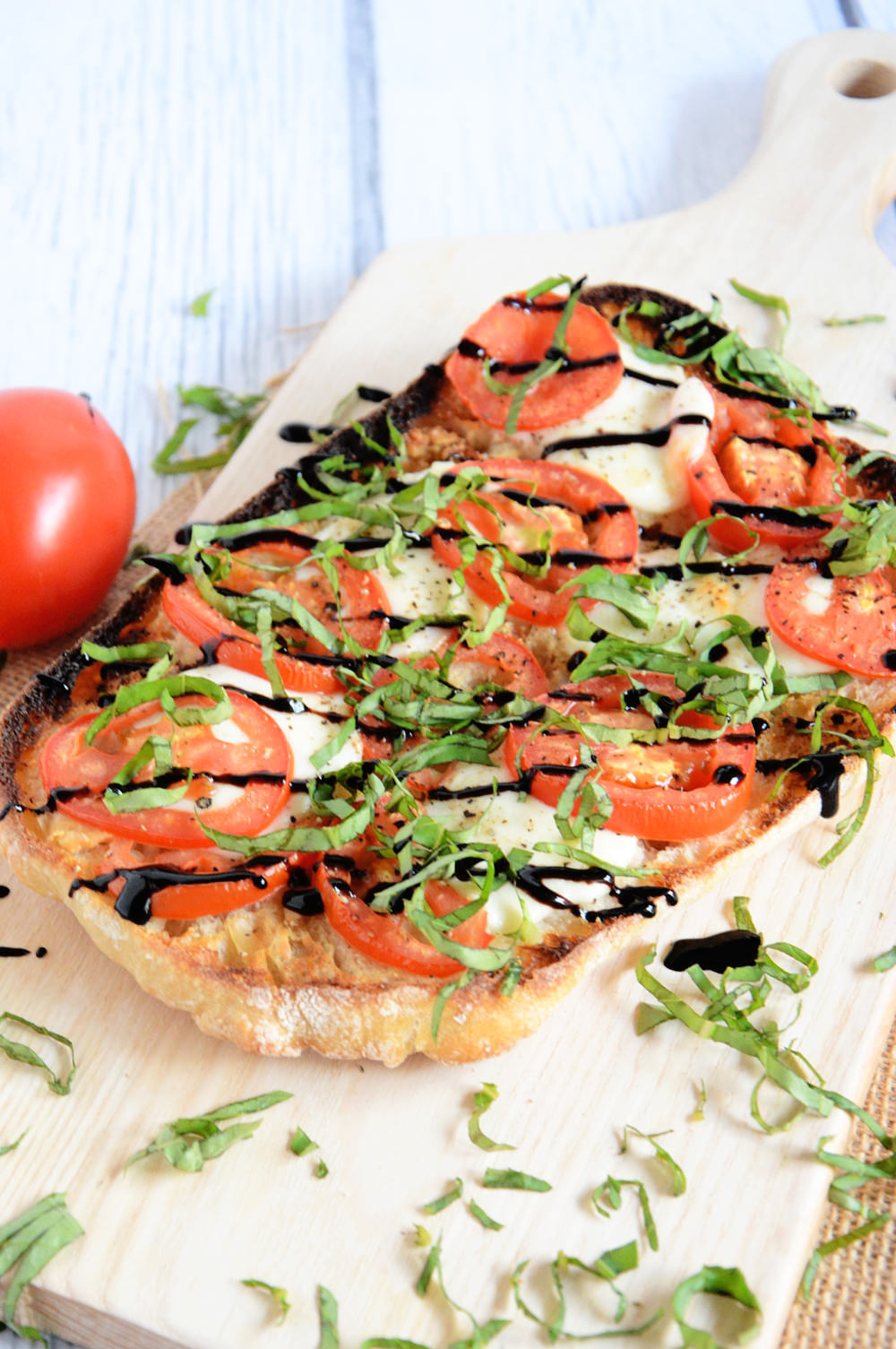 A Caprese Ciabatta Flatbread spiced up with a roasted garlic spread, roma tomatoes, fresh mozzarella and a balsamic drizzle! A simple and quick dinner!