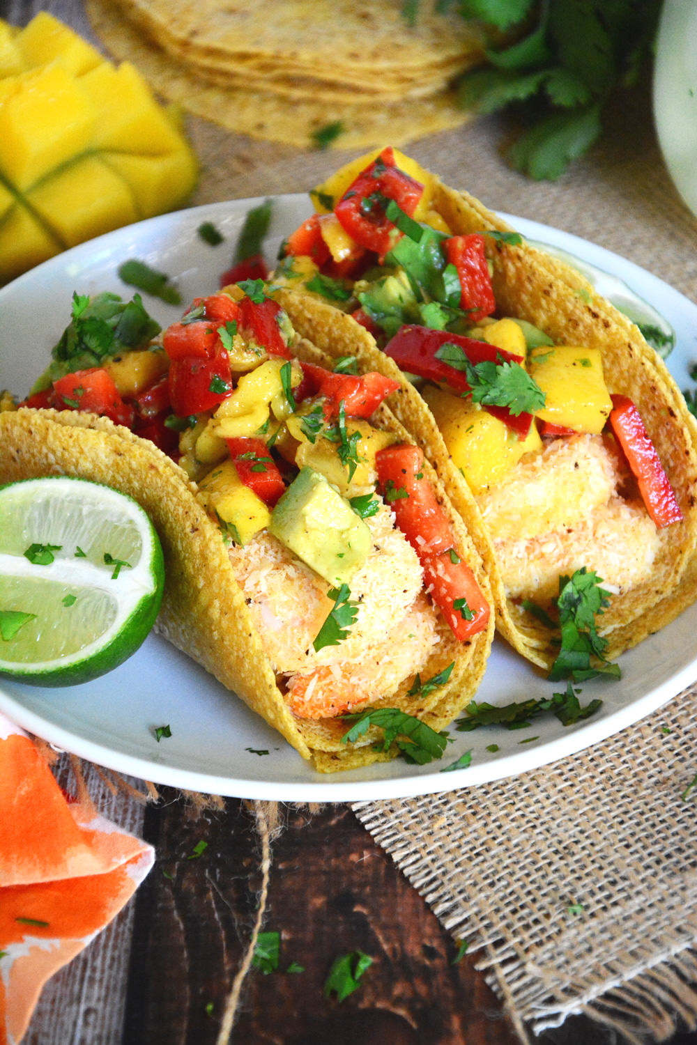 Healthy and Quick Shrimp Tacos sweetened with coconut and topped with a sweet and spicy salsa of mango, red pepper and avocado!