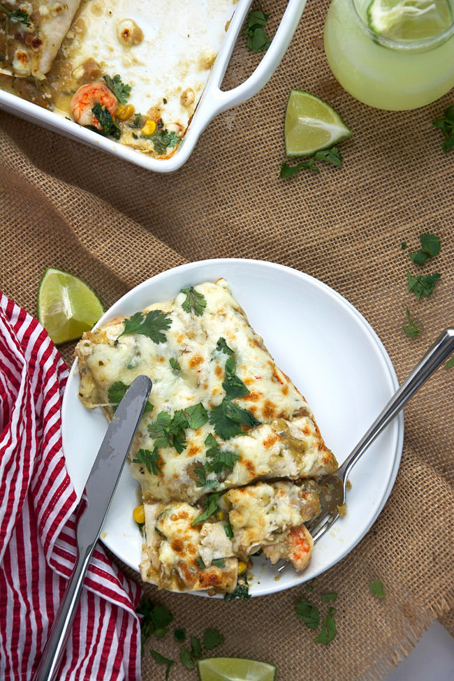 Shrimp enchiladas in a creamy salsa verde sauce lightened with greek yogurt, crisp corn, kale and creamy queso fresco!  #enchiladas #shrimp #texmex #glutenfree