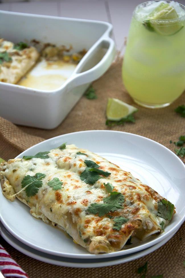 Shrimp enchiladas in a creamy salsa verde sauce lightened with greek yogurt, crisp corn, kale and creamy queso fresco!  #enchiladas #shrimp #texmex #glutenfree