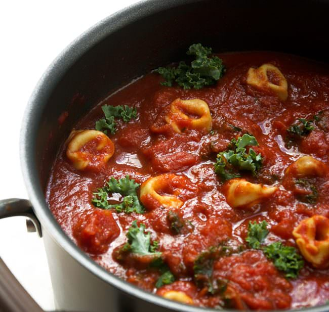 A creamy and rich tomato soup with kale and tortellini, made in only 15 minutes! Pure comfort food in no time! #tomatosoup #soup #tortellini #pasta
