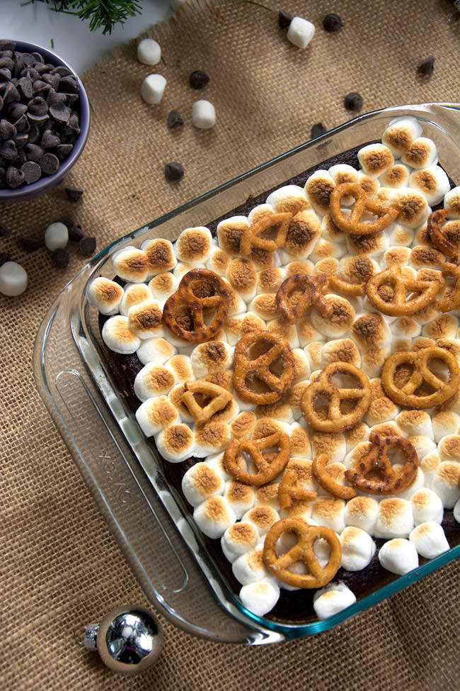 S'mores get an update with these Toasted Marshmallow Brownies as they are made healthier with oats, applesauce, two types of chocolate and then sit on top of cinnamon sugar pretzels! #smores #brownies #marshmallows #glutenfree