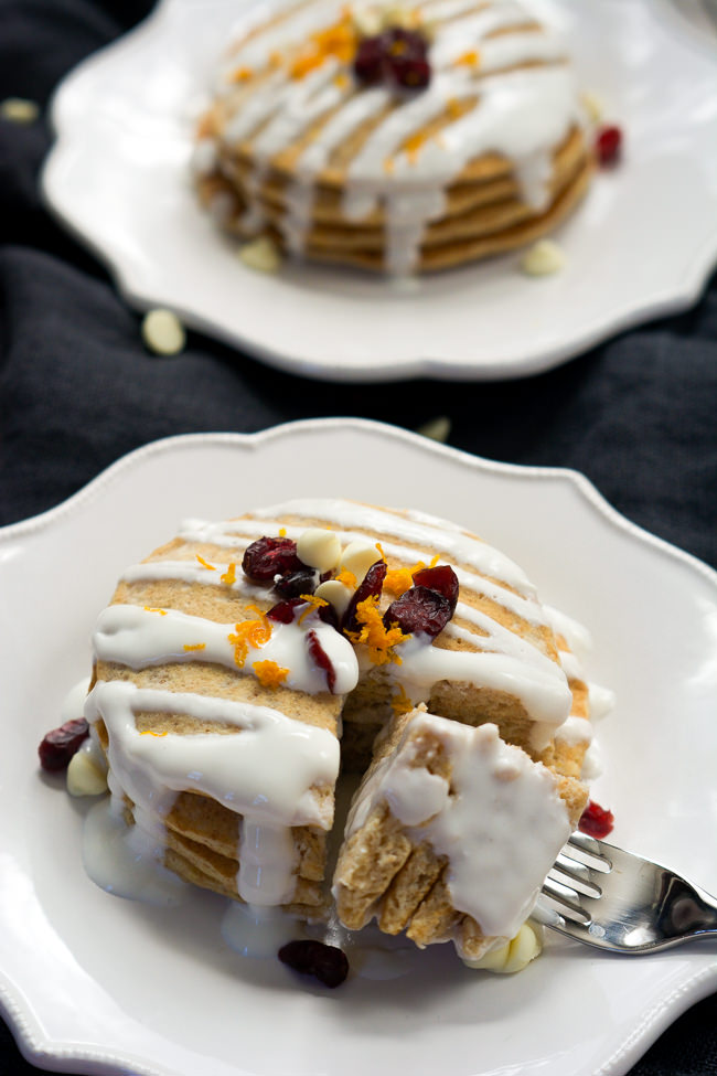 A Starbucks inspired breakfast, Whole Wheat Cranberry Bliss Pancakes are orange scented, studded with dried cranberries, filled with white chocolates and drizzled in a greek yogurt glaze!