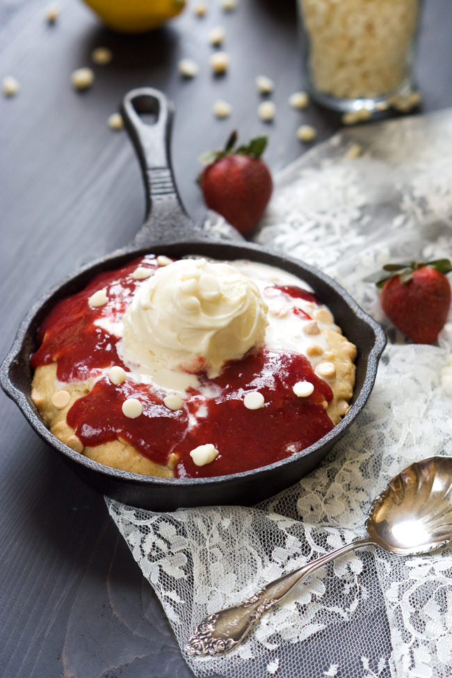 A decadent White Chocolate Sugar Cookie Skillet that is simple to make, topped with vanilla custard and drizzled with a gooey homemade strawberry sauce! #skillet #cookie #whitechocolate #icecream