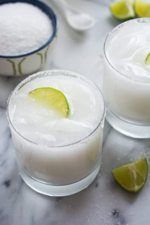 A tropical spin on the classic drink! These Skinny Coconut Margarita are made with lite coconut milk, coconut water, tequila blanco and triple sec for a refreshing cocktail!