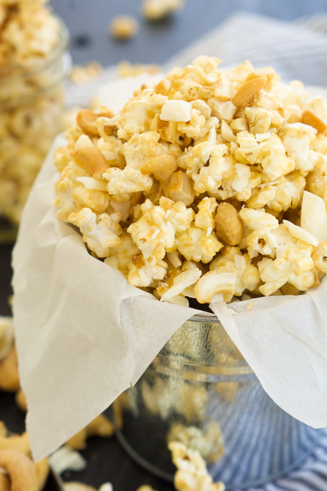 A sweet and salty treat that takes minutes to make! Skinny Peanut Butter Caramel Popcorn is made with only natural ingredients and is tossed with cashews and white chocolate for a sweet treat!
