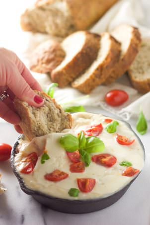 All the flavors of your favorite salad in an appetizer! Skinny Hot Caprese Dip is lighter thanks to a secret ingredient, greek yogurt, gooey mozzarella, tomatoes and fresh basil!