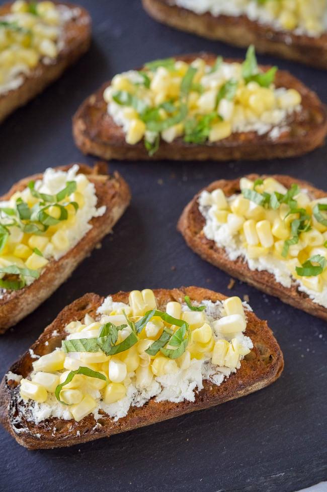 Crisp Corn Crostini on Garlic Baguettes are a quick, noncook appetizer that has fresh corn, garlic, creamy goat cheese all spread over a whole grain baguette!