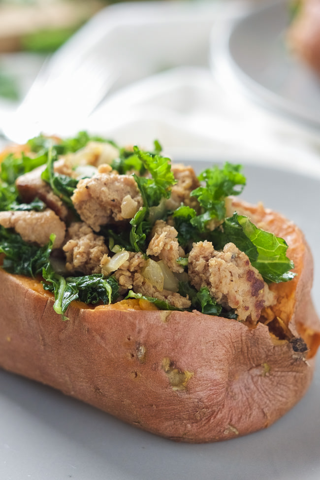Kale and Sausage Stuffed Sweet Potatoes are an easy dinner idea, filled with sweet sausage and smothered in an easy white cheese sauce!