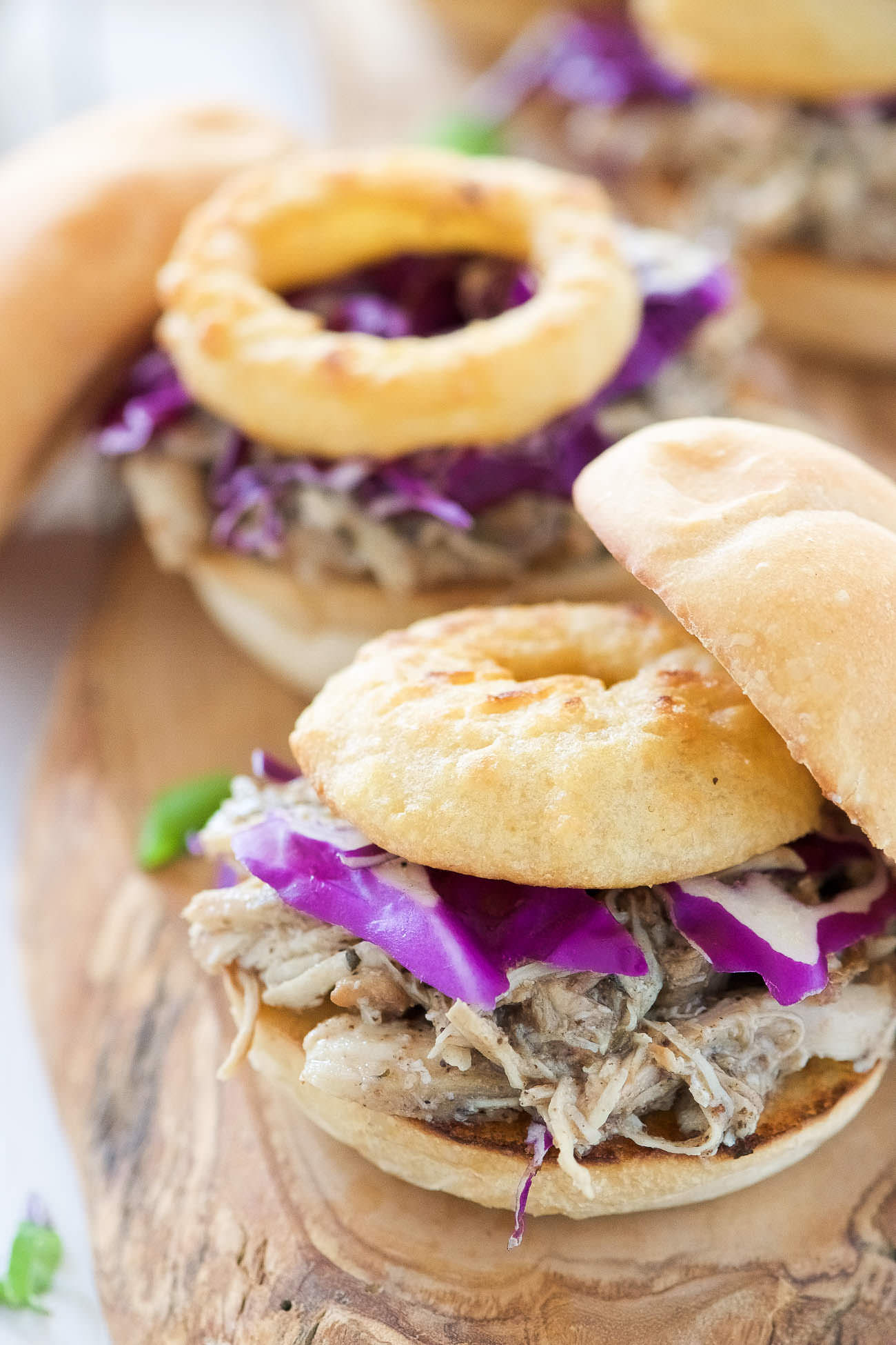 Brown Sugar Pulled Chicken Sandwiches have the most tender, slightly sweet chicken! The slow cooker makes dinner a breeze for these sliders that are topped with a tangy homemade honey mustard sauce and crispy onion rings. Perfect for dinner, get togethers or game day!