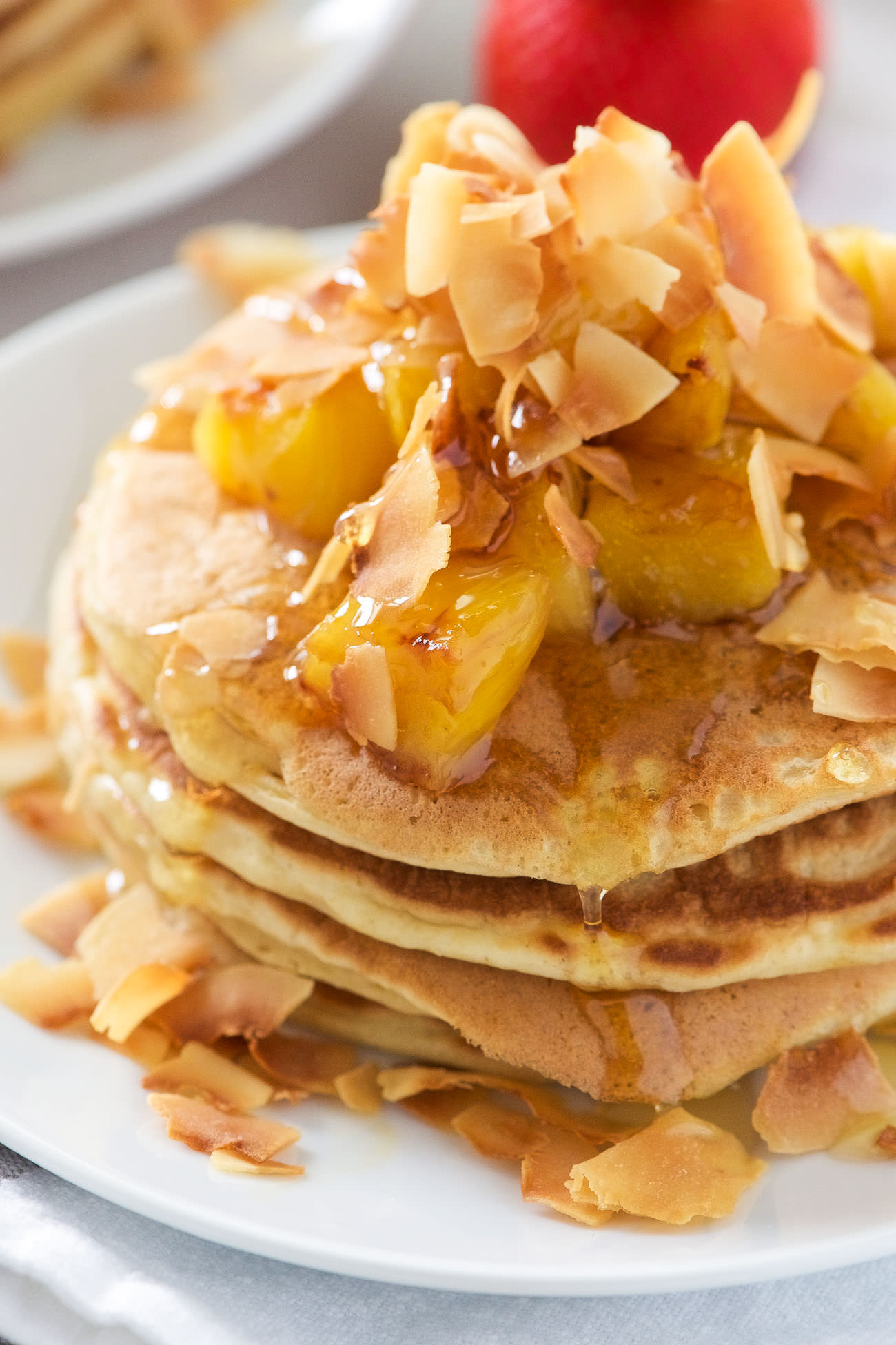 These Honey Pineapple and Toasted Coconut Pancakes are light, fluffy and filled with tropical flavors! These pancakes are the perfect start to a weekend breakfast or brunch!
