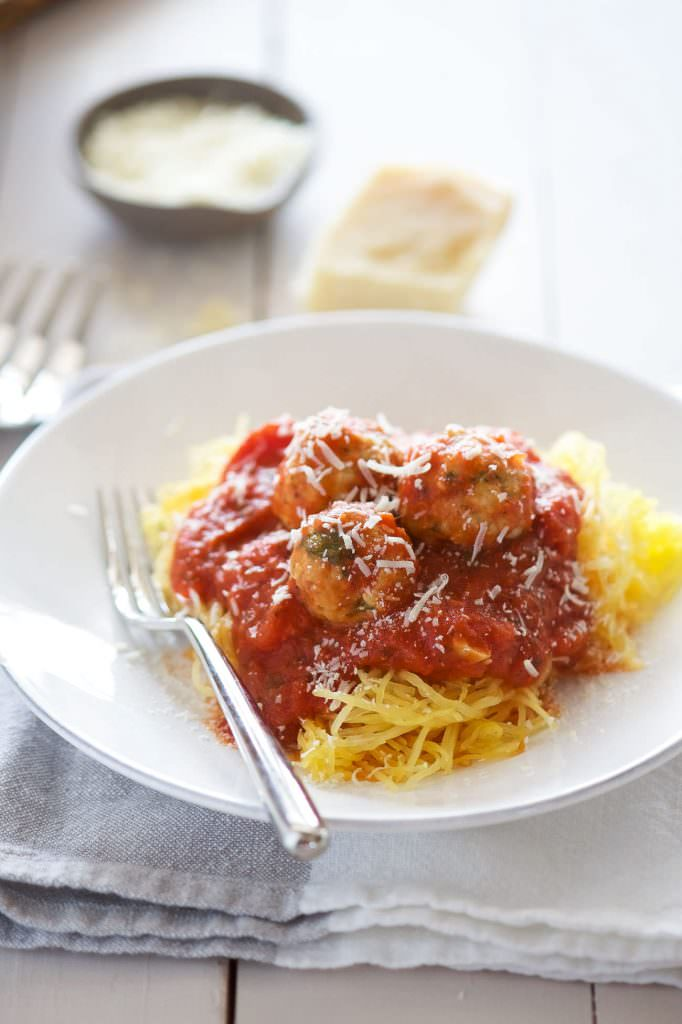 Skinny Sun Dried Tomato Meatballs with Spaghetti Squash are a light and flavorful way to cure your craving for spaghetti and meatballs! Lean ground turkey is mixed with sun dried tomatoes and spinach. Perfect to make ahead, freeze then bake before serving!
