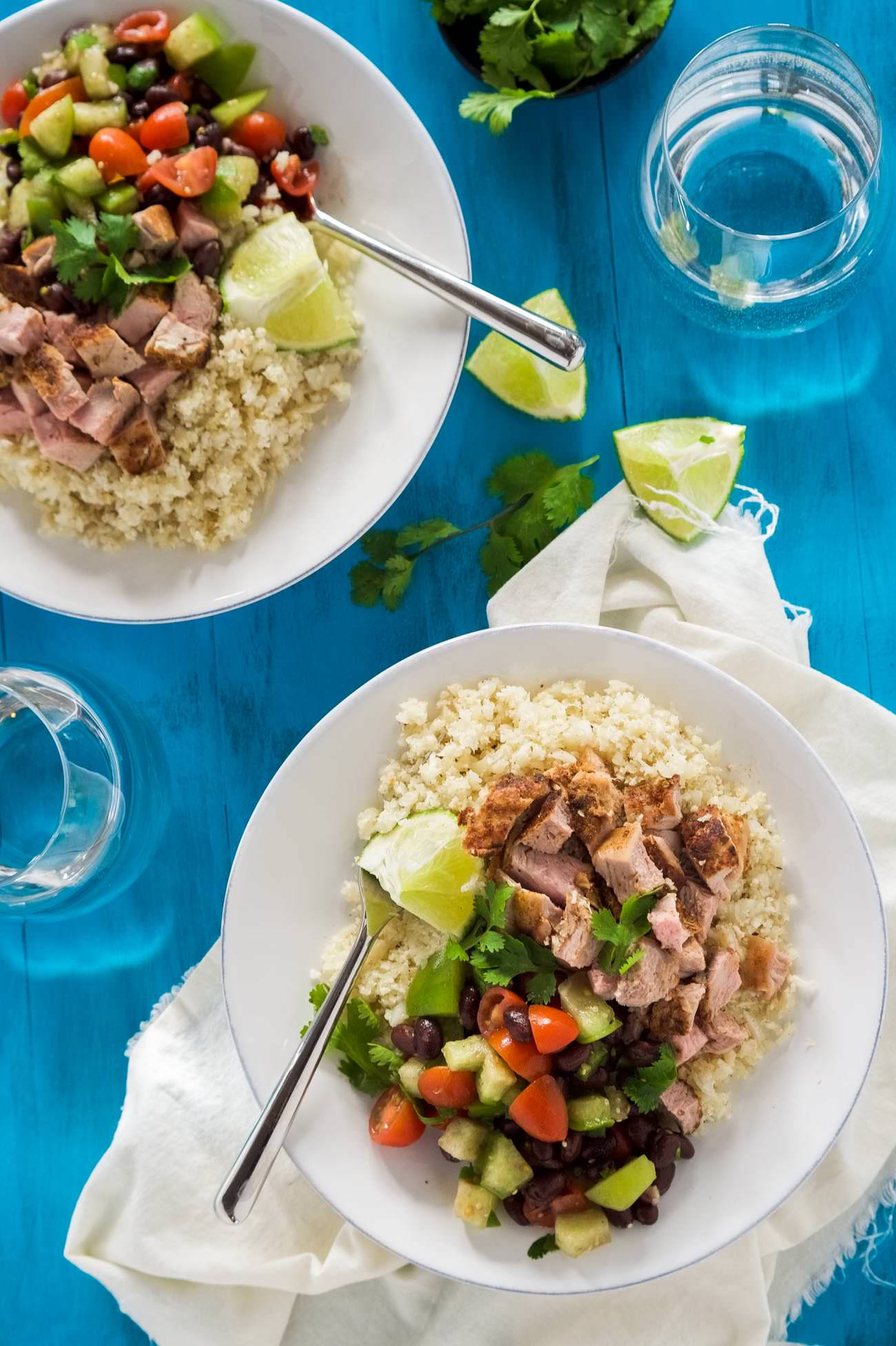 Chipotle Pork Carnita Burrito Bowls with Cumin Lime Rice are a healthy, homemade tex mex favorite! Filled with juicy, spiced pork, a homemade black bean salsa and lightened up cumin lime cauliflower rice!