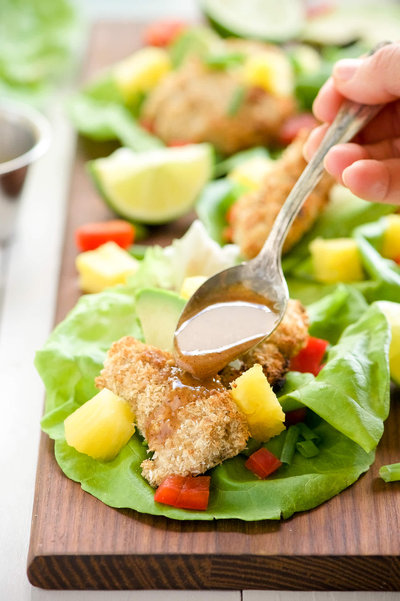 Cashew Coconut Crusted Chicken Lettuce Wraps are our new favorite hand held dinner! Every bite of chicken is encrusted in crunchy cashews and coconut then drizzled with a sweet and spicy Ancho Honey Mustard Sauce!