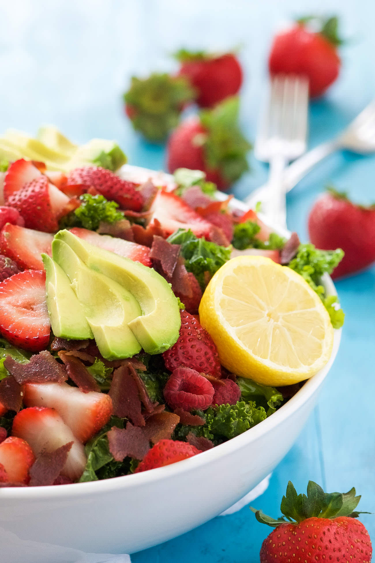 This Bacon & Berry Kale Salad with Honey Lemon Vinaigrette is a summertime superfood salad! Fresh kale tossed in a honey lemon vinaigrette and topped with fresh berries, creamy avocado, and crispy bacon!