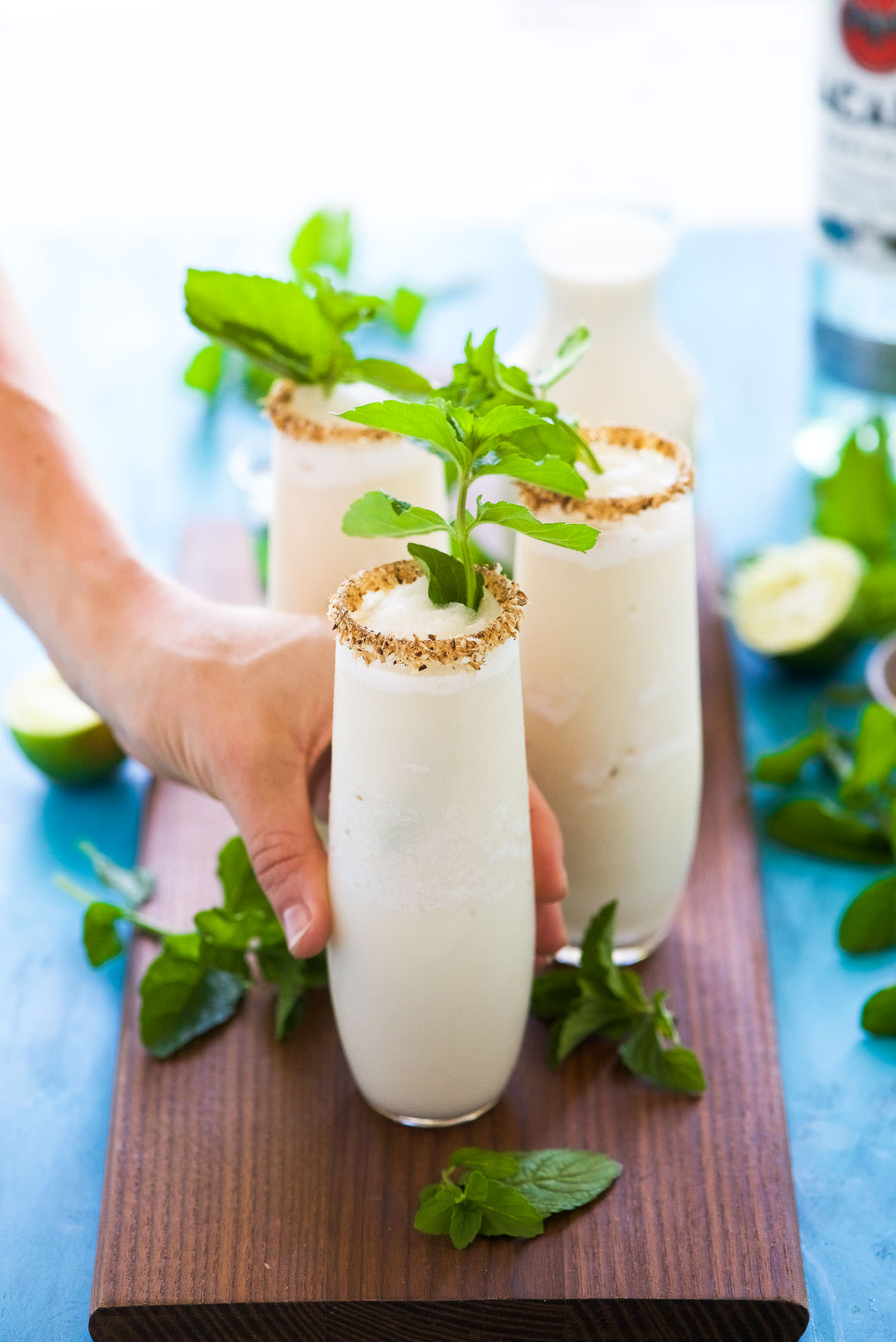This Toasted Frozen Coconut Mojito is a summer must have! Made lighter with fresh lime juice, a mint simple syrup, and then blended with coconut milk for a refreshing cocktail that you won't have trouble asking for seconds!