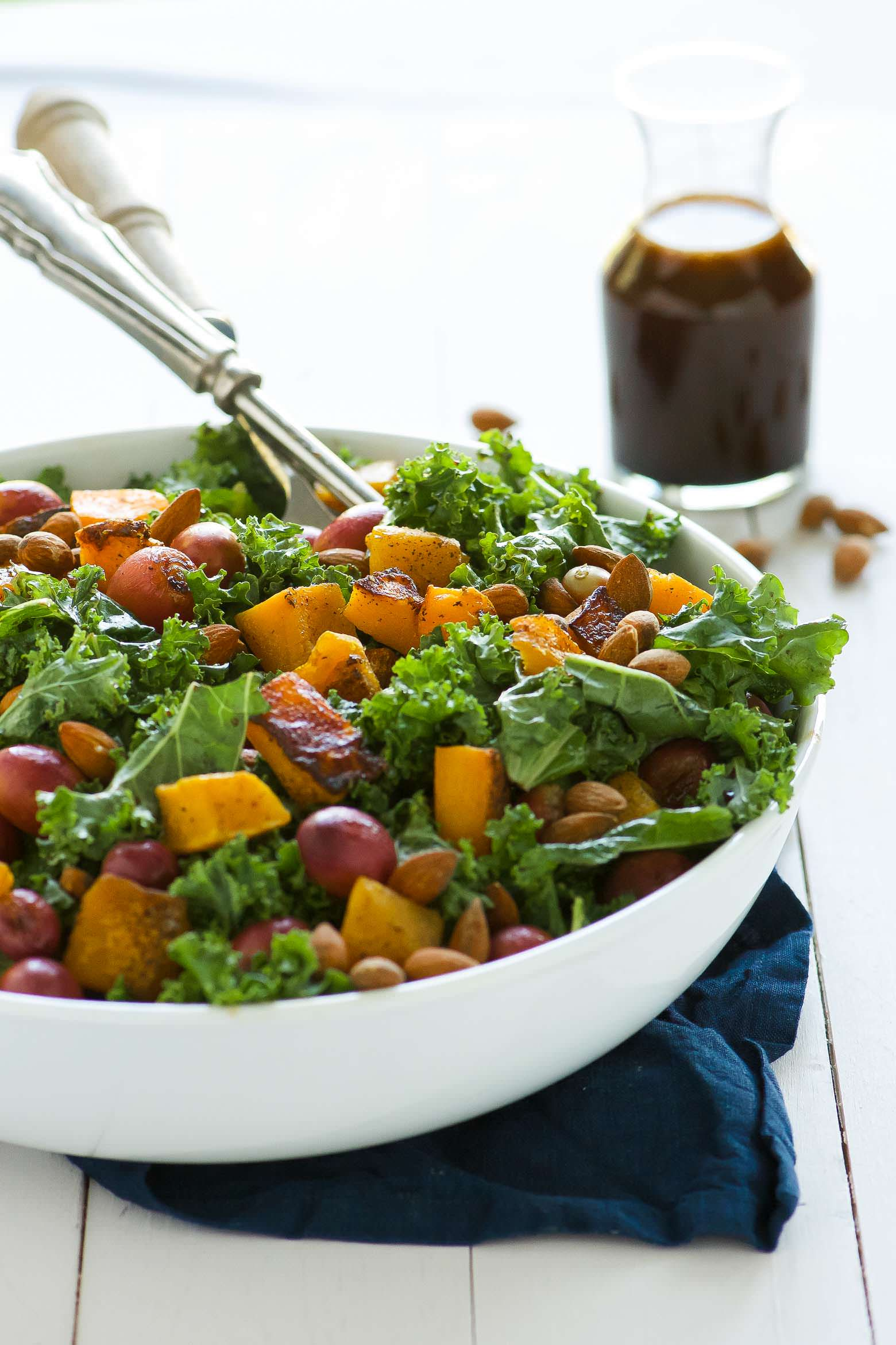 Massaged Kale Salad with Butternut Squash and Roasted Grapes is fall in a dish! It is healthy, simple and perfect for make-ahead lunches! Caramelized butternut squash and roasted grapes mix with balsamic massaged kale for a paleo and vegan friendly salad!