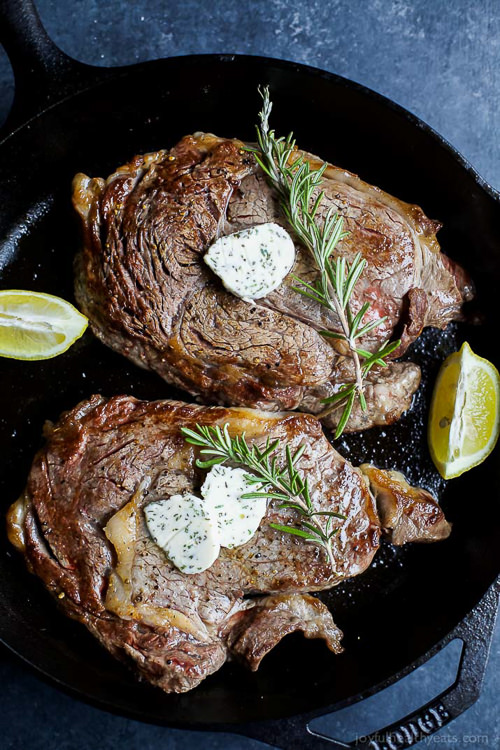 The perfect steak in just 15 minutes! Pan Seared Ribeye that's finished off in the oven and topped with homemade Herb Butter that will make you swoon!