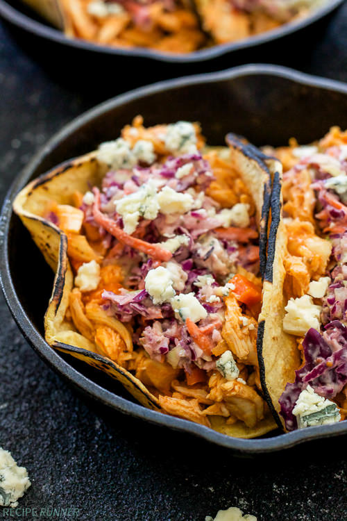 Shredded chicken coated in buffalo sauce and topped with a creamy blue cheese coleslaw. These easy to make slow cooker Buffalo Chicken Tacos with Blue Cheese Coleslaw are perfect for a weeknight dinner or serve them up on game day!