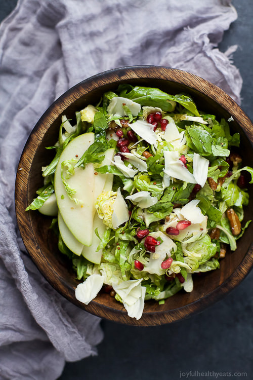Shaved Brussel Sprout Salad filled with apples, pomegranate, candied pecans, and white cheddar cheese then tossed with a light Lemon Vinaigrette. This Brussel Sprout Salad is the perfect side dish for the holidays!