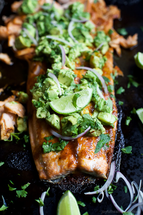 Paleo Baked Salmon that's rubbed down with a sweet & spicy spice blend then topped with a fresh zesty Avocado Salsa! This easy healthy recipe is done in less than 30 minutes!